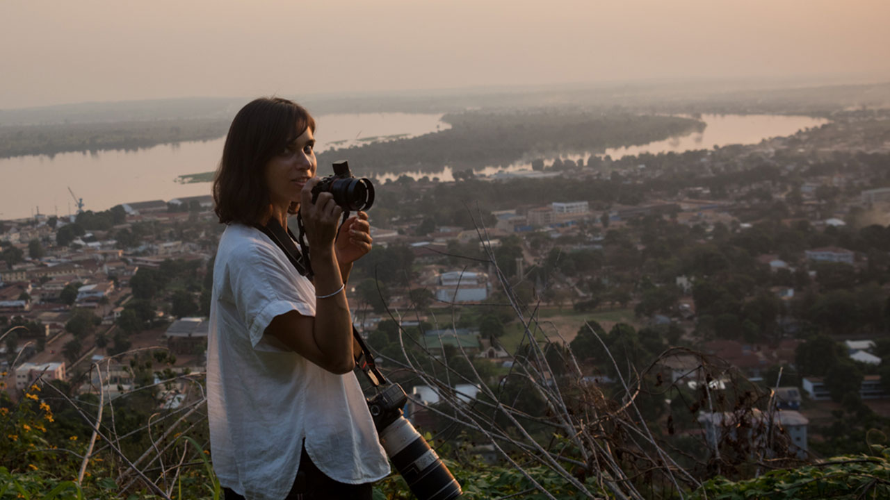 Photojournalist in front of a city