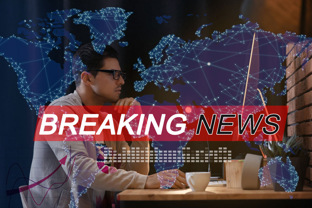 Breaking News - Man at computer desk with map overlayed behind him