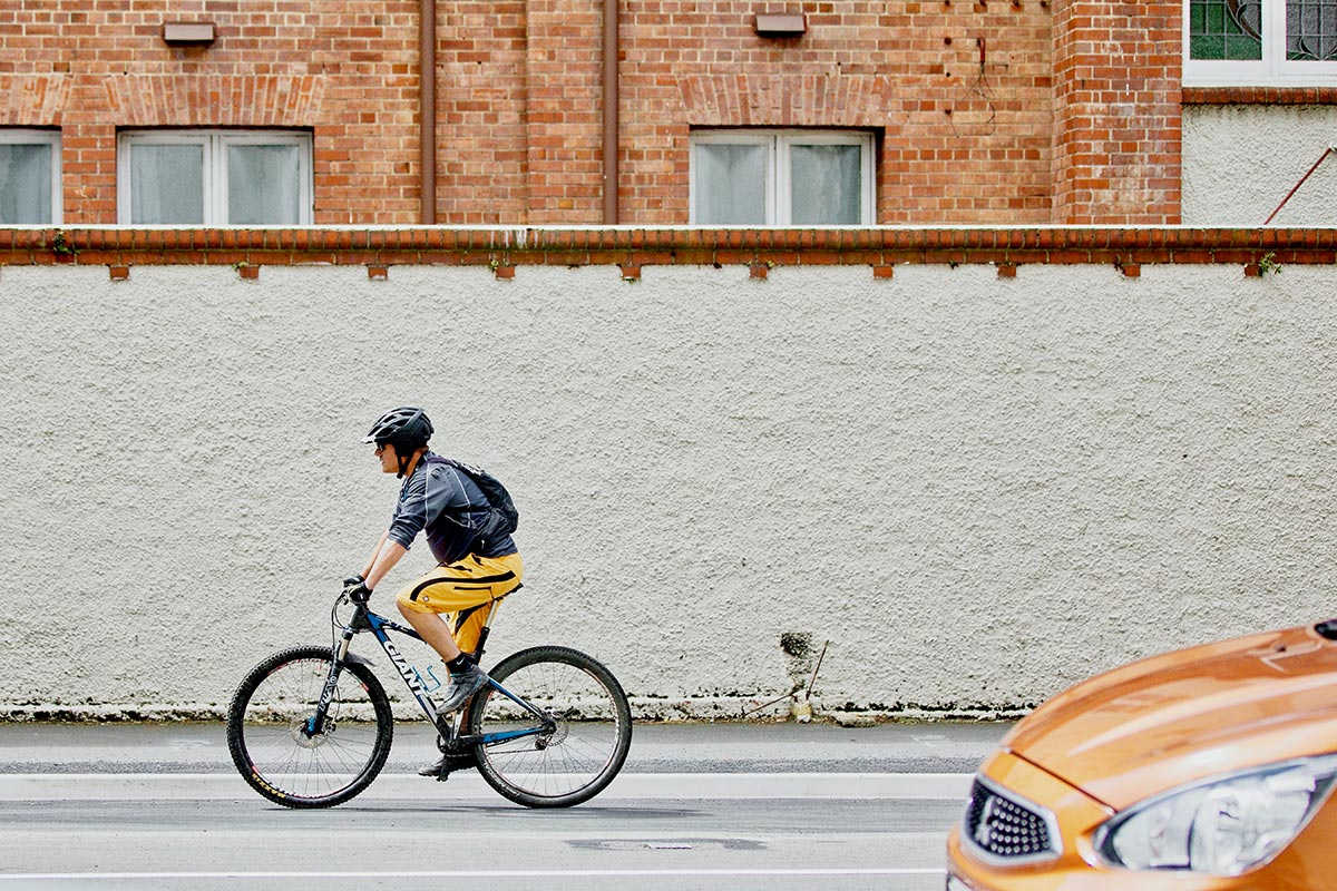 Cyclist driving alongside road in front of a wall