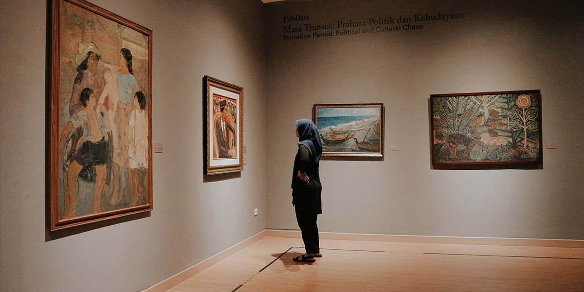 Person looking at paintings at museum