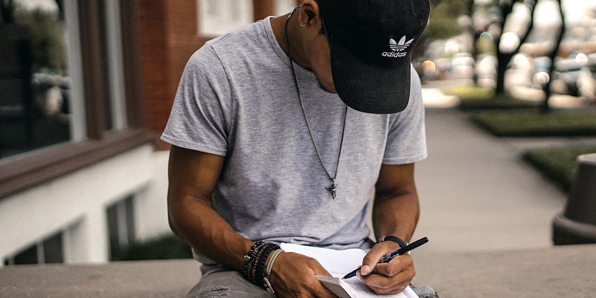 Writer writing in notebook outside