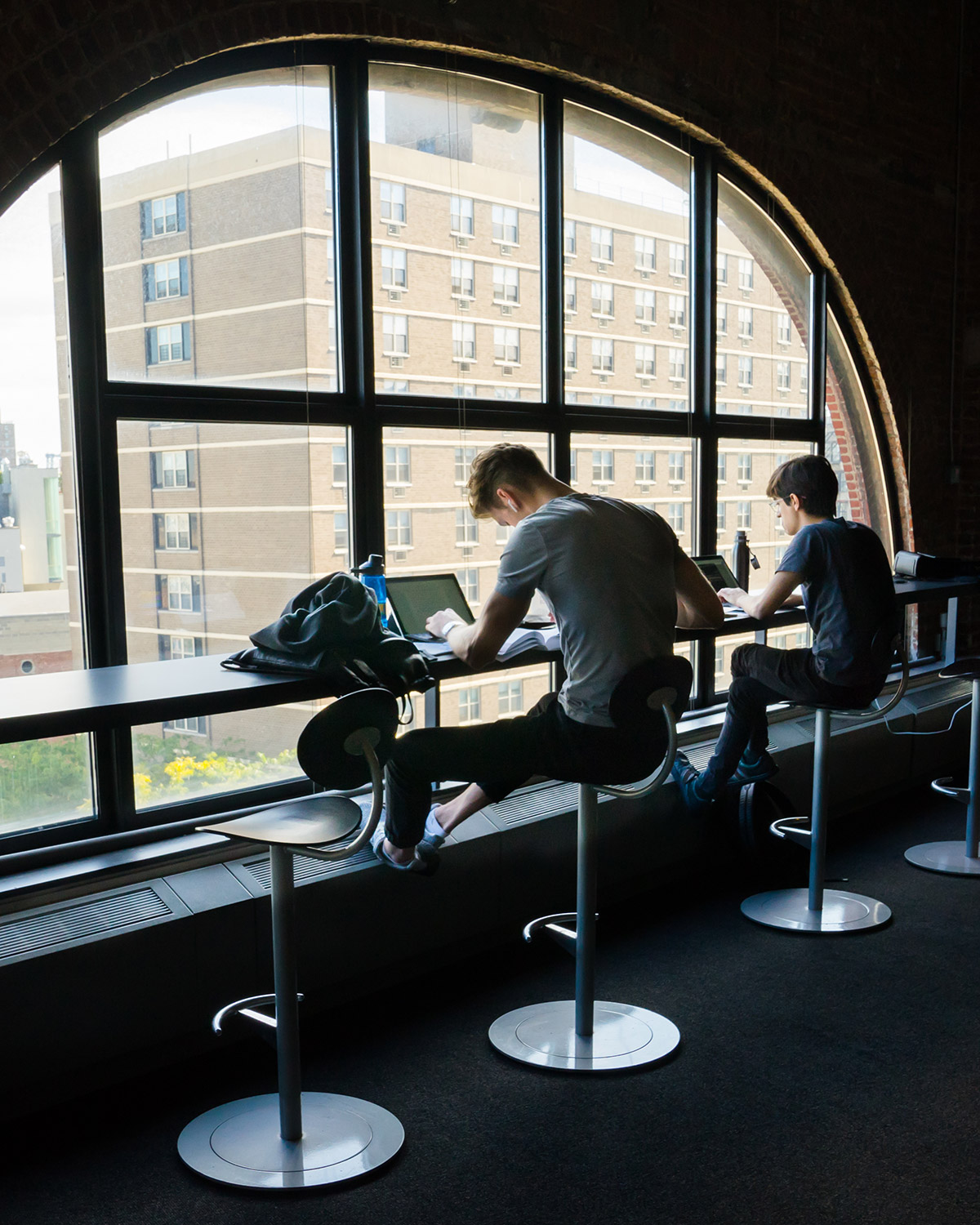 Students studying at window in common area