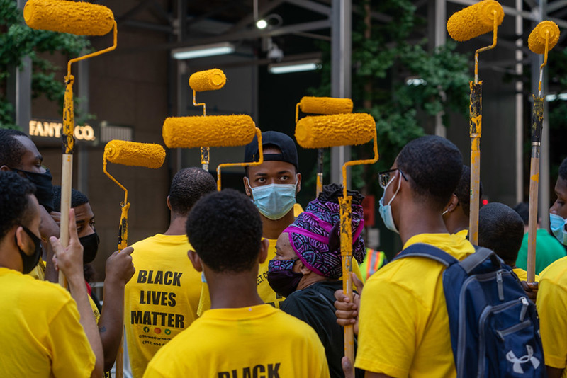 "Young volunteers lift paint rollers used to write ""Black Lives Matter"" in front of Trump Tower on Manhattan's famed 5th Avenue. July 9, 2020. Photo by NYU Journalism's Thomas Hengge."