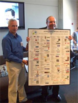 Sean Mulligan (SERP 1) presents Bill Burrows with a poster listing many of the places alumni have gone to work during the first 25 years of the program Burrows founded in 1982.